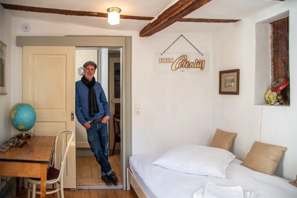 Der Großvater von Dirk Melzer führte bis 1980 das Eisenwarengeschäft Colonius in St. Goarshausen, aus dem einige Sammlerstücke wie auch das kolorierte Foto links über dem Schreibtisch stammt. (Foto: Andrea Schwappach)